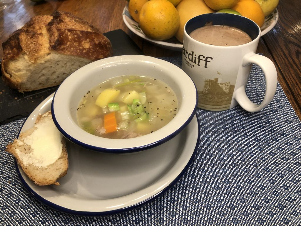 Welsh Recipe: a bowl of cawl, or Welsh lamb soup with a slice of buttered bread and mug of tea